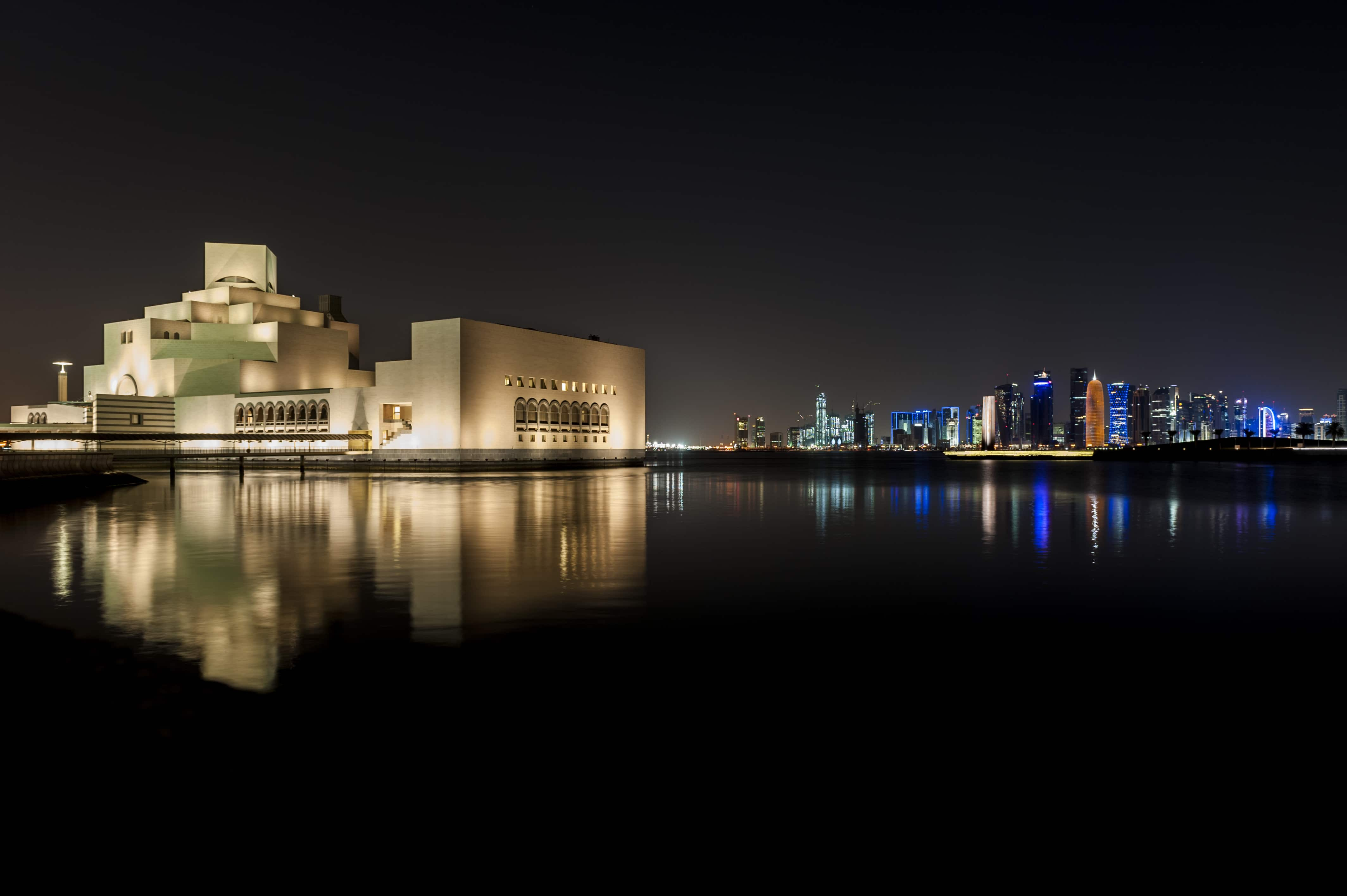 Night shot of the Museum of Islamic Art with reflection and the Doha skyline in the background.